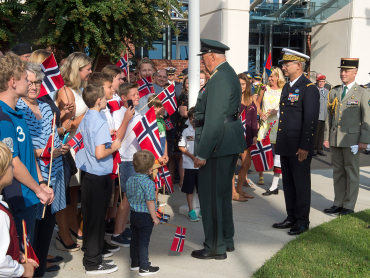 King Harald spoke with some of the children that greeted him on his arrival at the NATO Headquarters. Photo: NATO