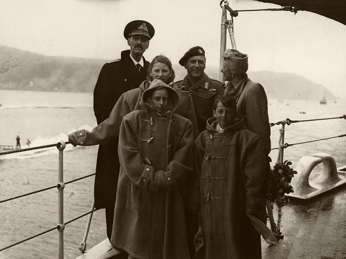 HSE Norfolk in the Oslo fjord, returning home to a free Norway. It was a cold, cloudy day, and the children borrowed warm clothes from the crew. Photo: Royal Navy/The Royal Collections.