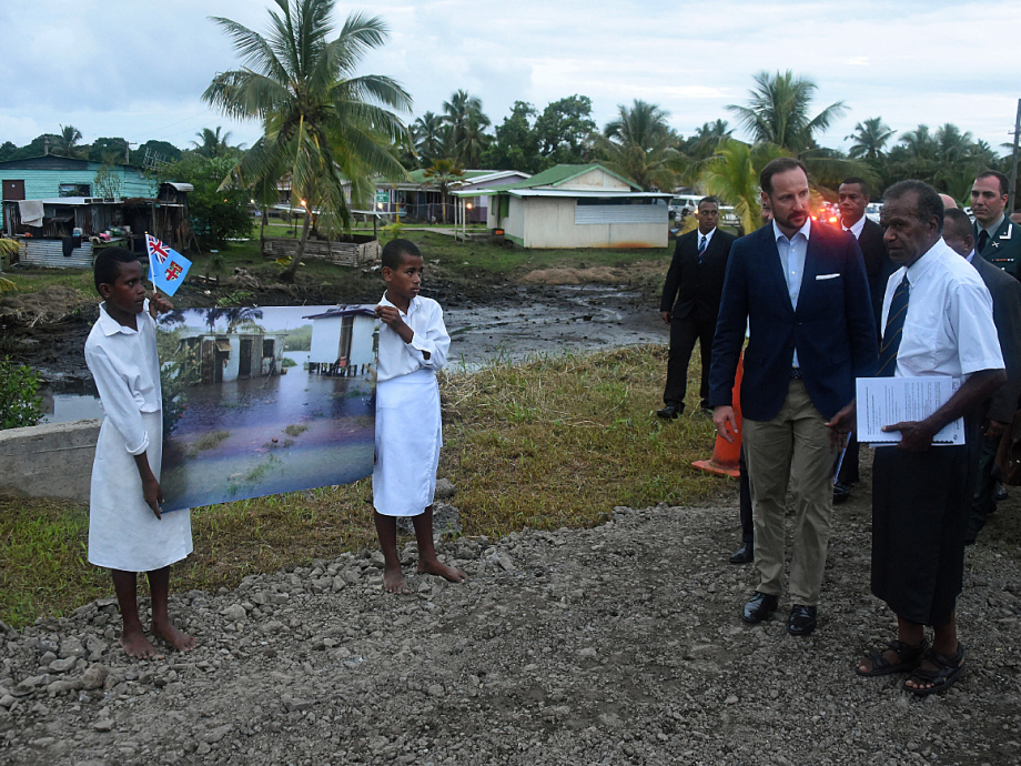 Children show pictures of how flood water has inundated the village. Photo: Sven Gj. Gjeruldsen, The Royal Court